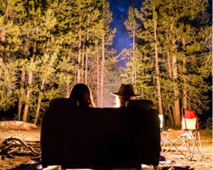 Couple surrounded by tall trees at night in front of a campfire